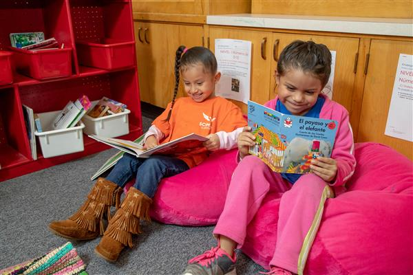 two elementary students reading Spanish books sit on pink beanbags