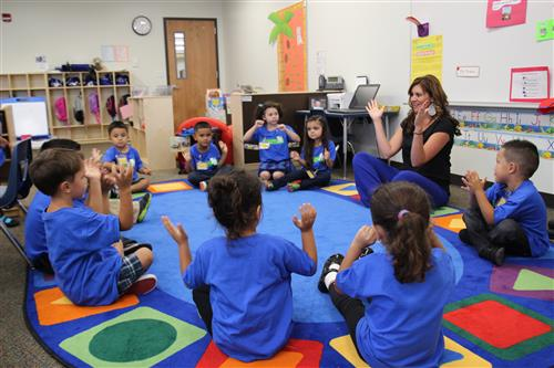 Teacher and students in classroom clapping their hands while sitting in a circle