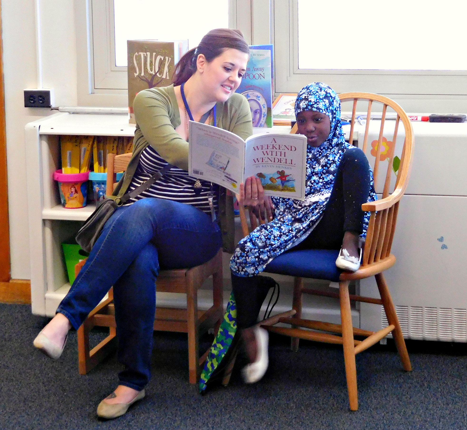 DPS Volunteer reading with student near windows